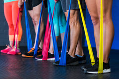 Athletes exercising with resistance band in gym Royalty Free Stock Images