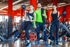 Athletes in the gym are posing with a hammer and a rope.