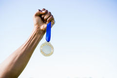 Athletes hand holding gold medal after victory Royalty Free Stock Image