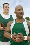 Athletes Holding Shot Put And Discus. Male athletes holding shot put and discus while looking away Stock Image