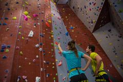 Athletes interacting while standing by climbing wall in gym. Low angle view of athletes interacting while standing by climbing wall in gym Royalty Free Stock Images