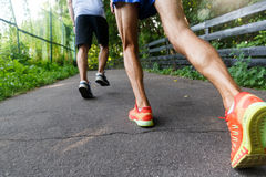 Athletes jogging in the park. Legs closeup stock images