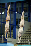 Athletes jump from diving-tower at competition. MOSCOW - APR 13:  Athletes jump from diving-tower at competitions on syncronized springboard diving in Pool of SC Stock Photography