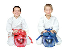 Athletes in kimono sitting in a ritual pose karate with helmets isolated. Athletes in kimono sitting in a ritual pose karate with helmets Royalty Free Stock Image