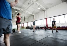 Athletes Lifting Kettlebell And Jumping Ropes In Fitness Center Stock Photography