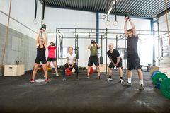Athletes Lifting Kettlebells in Cross Fitness Box. Group of young male and female athletes lifting kettlebells at cross training box Stock Photography