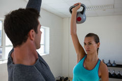 Athletes lifting kettlebells while facing each other in club. Confident athletes lifting kettlebells while facing each other in club Stock Photography