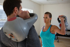 Athletes lifting kettlebells while facing each other. In gym Royalty Free Stock Photo