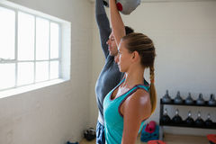 Athletes lifting kettlebells in gym. Side view of athletes lifting kettlebells in gym Stock Images