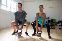 Athletes lifting kettlebells in health club. Full length of athletes lifting kettlebells in health club Stock Images