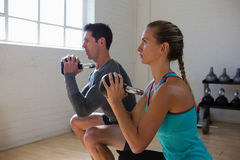 Athletes looking away while exercising with kettlebells. In club Stock Photo