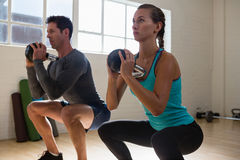 Athletes looking away while lifting kettlebells. In gym Stock Photo