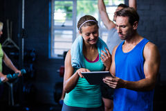 Athletes looking in tablet computer at gym Royalty Free Stock Photography