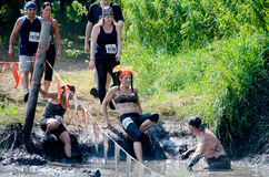 Athletes moving into the mud. A group of athletes step carefully into the mud river at the 2014 Indiana mudathlon Royalty Free Stock Image