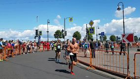 Athletes at one of the turns of the St. Petersburg marathon. Support from spectators at a distance
