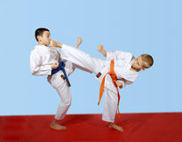 Athletes perform paired exercises beat kicks. On the mat Royalty Free Stock Photos
