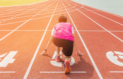 Athletes preparing for race on starting blocks. Royalty Free Stock Image