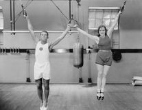 Athletes on rings in gym Royalty Free Stock Images