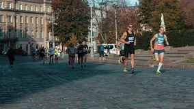 Athletes run down the street of the city. LVIV, UKRAINE - OCT 13, 2019: Athletes run down the street of the city competing for the championship in the running stock video