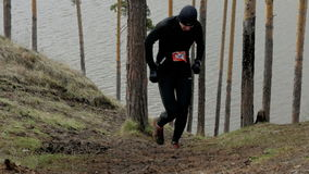 Athletes runner man rises into a steep mountain. Ekaterinburg, Russia -  April 24, 2016: slow motion athletes runner man rises into a steep mountain during stock footage