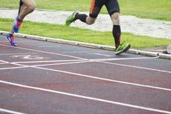 Athletes running outdoors. Athletes running on the athletics track Stock Image
