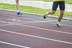 Athletes running outdoors. Athletes running on the athletics track Royalty Free Stock Photos