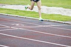 Athletes running outdoors. Athletes running on the athletics track Royalty Free Stock Image