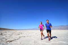 Athletes running sport fitness couple outdoor. Multiracial couple of runners training outdoors in fitness clothing under burning sun in desert. Caucasian men stock image