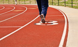 Athletes running on synthetic track. Picture of a red synthetic running track with athletes running on it Stock Photos