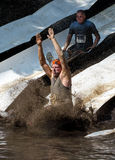 Athletes sliding  into the mud. Two men plunge into the muddy pond at the 2014 Indiana mudathlon Stock Photography