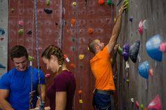 Athletes standing by trainer climbing wall. In gym Stock Image