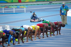 Athletes at start line of 100m sprint run Stock Photo