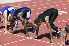 Athletes At The Starting Line. Multiethnic male athletes at starting line in track race Royalty Free Stock Photo
