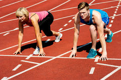 Athletes at starting line on race track Stock Photo