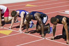 Athletes At Starting Line On Racetrack. Multiethnic male athletes at starting line on racetrack Royalty Free Stock Image