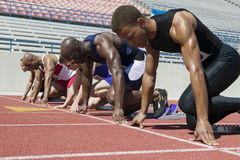 Athletes At A Starting Line On Racetrack. Group of multiracial male athletes at a starting line on racetrack Royalty Free Stock Photos