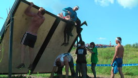 Athletes storm wall in extrim race. Tyumen.Russia stock video footage