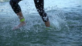 Athletes swimmers changing race discipline from swimming to biking on river. Open water triathlon long distance ironman triathlon competition. Healthy stock video