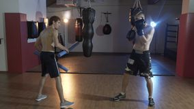 Athletes train in the gym. Preparation of the boxer for battle. The coach works with the boxer speed and accuracy of. Impact. Training boxer, gloves for boxing stock footage