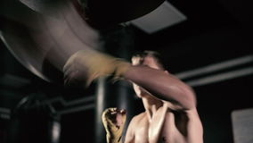 Athletes train impact on accuracy and speed. Boxer has an attempt on pneumatic punching bag. Young man shirtless trains in the boxing hall stock footage