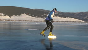 Athletes train at Lake Baikal. Sportive man are skating on the ice of frozen Baikal during sunset. Outdoor winter fun for athlete nice winter weather stock footage