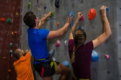 Athletes with trainer climbing wall in gym. Rear view of athletes with trainer climbing wall in gym Stock Images