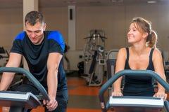 Athletes training on exercise bikes at gym Stock Photos