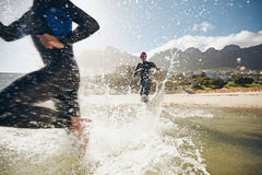 Athletes training for a triathlon. Image of triathletes rushing into the water. Athlete running into the water, training for a triathlon Royalty Free Stock Photos