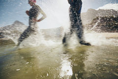 Athletes training for triathlon race. Image of splashes of water while triathletes running in lake. Athletes training for triathlon race stock photo