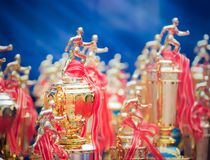 Athletes trophy cup awards with a red ribbon. Group of runner trophy on the blue background royalty free stock photo