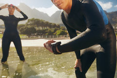 Athletes in wet suits preparing for triathlon competition. Man checking his timer. Athletes in wet suits preparing for triathlon competition Stock Photography