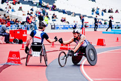 Athletes on wheelchairs shaking hands. Athletes at the Visa London Disability Athletics Challenge at the Olympic Stadium in London on May 8, 2012. The event is Royalty Free Stock Photography