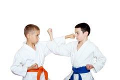 Athletes in a white kimono perform exercises karate Stock Photos