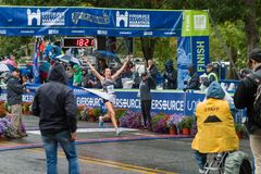 Athletes Winning crossing finish line in street marathon stock photo